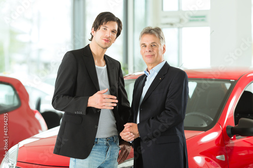 Mature and young man with autos in car dealership