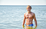 Semi nude handsome smiling man standing in the sea