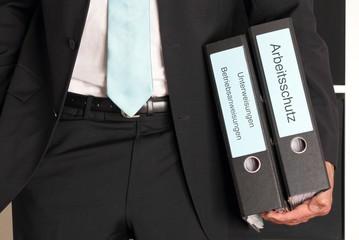 Mann im Anzug haelt zwei Arbeitsschutz Ordner unter Arm