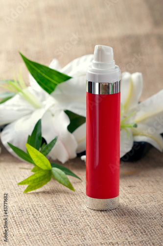 Bottle of face/body cream/lotion with lily flowers