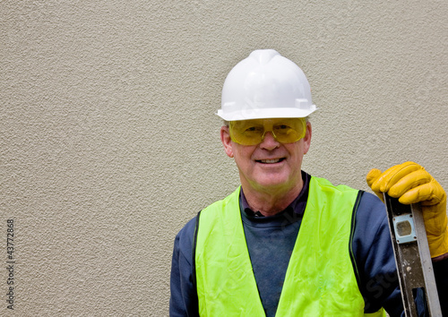 Construction worker leans on spirit level