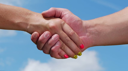 A man and woman shaking hands on blue sky background