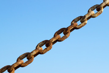 Old rusty metal chain links and a blue sky.