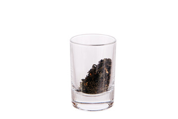 Shot glass filled with batch of dry green tea