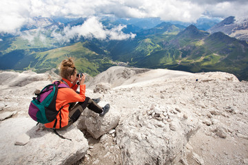 cute girl taking pictures of beautiful panorama in the alps