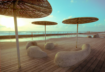 Wooden deck with stone benches and metal with straw umbrellas