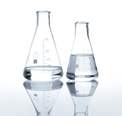 Two laboratory flasks with a clear liquid, isolated