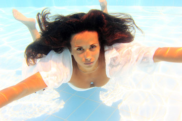 Woman wearing a white shirt swimming underwater