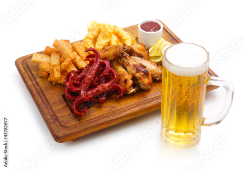Closeup of spicy appetizer and glass of beer isolated