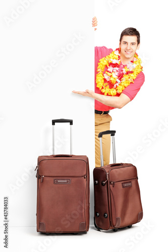 Young man with suitcases posing behind panel