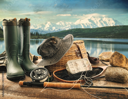 Staande foto Vissen Fly fishing equipment on deck with view of a lake and mountains