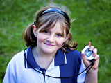 Happy young girl  checks stop watch at school sports day