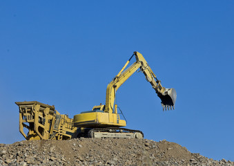 Excavator loading soil into large spreading container