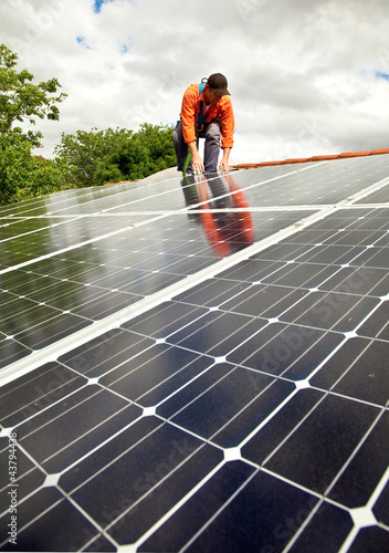 Electrician checking solar panels on roof