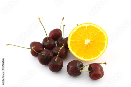 Half navel orange and cherry on white background