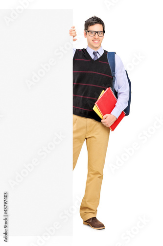 Full length portrait of a male student posing behind a panel