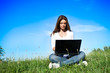 Woman with laptop in the meadow