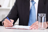 Businessman writes with  pen on paperwork