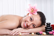 Smiling woman in spa salon, stone massage