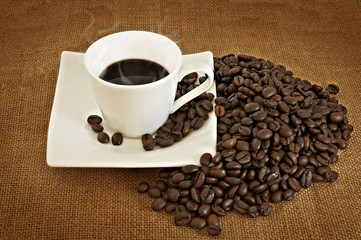 Heap of coffee beans and coffe cup