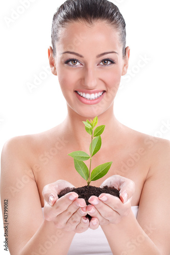 Beautiful girl holding young growing plant