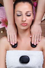young woman having a massage  with stone in a spa