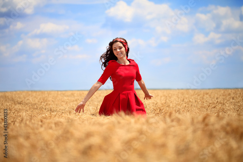 Girl in a red dress walking through wheat field.