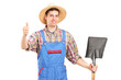A male agricultural worker holding a shovel and giving a thumb u
