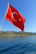 Flag of Turkey against the sea and mountains