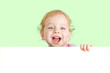 Happy child face behind blank advertising banner. Banner and gre
