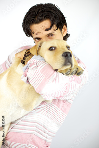 Young man kissing his puppy dog labrador