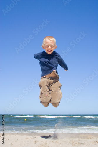 Smiling boy jumping on a beach