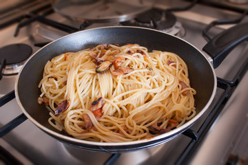 Spaghetti with clams into frying pan on stoves