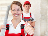 Young worker fixing up a house and showing thumb u