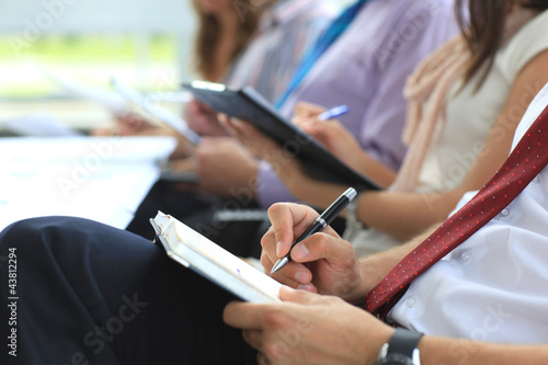 Closeup of executive writing notes during business meeting