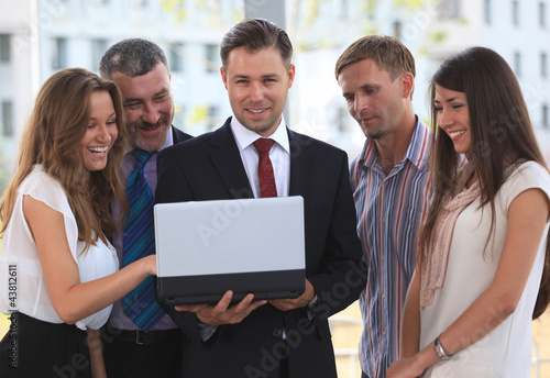 business team discussing while looking at laptop together