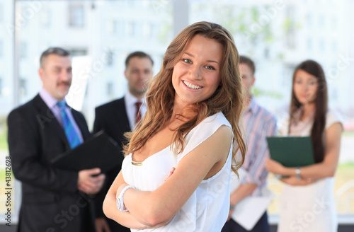 Successful business woman standing with her staff at office