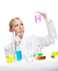 Young lady scientist stares at the beaker, isolated on white
