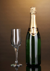 Bottle of champagne and goblet on brown background