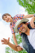 Portrait of smiling father giving his son piggyback ride outdoor