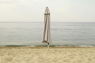 End of summer. Closed parasol on an empty beach