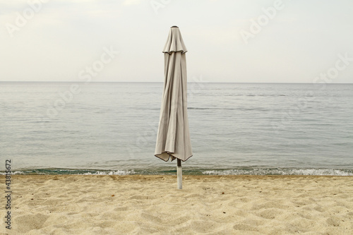 End of summer. Closed parasol on an empty beach - 43815672