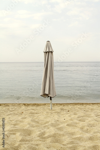 End of summer. Closed parasol on an empty beach - 43815673