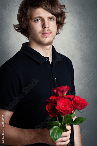 sad young man with bouquet of a red roses