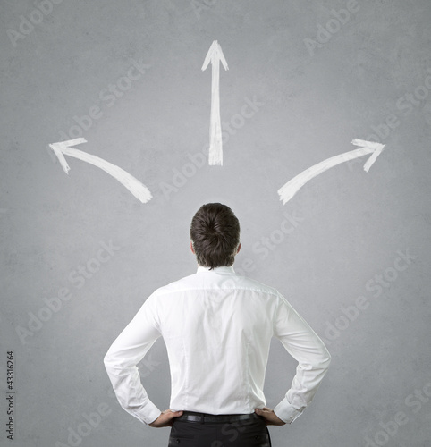 Confused, young businessman looking at chalk drawn arrows