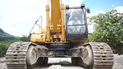 Heavy equipment excavator running over the camera or viewer.