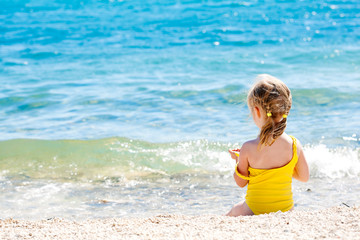 Small caucasian girl sitting on the shore of the sea