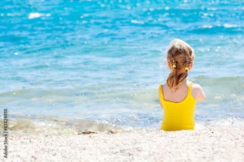 Small caucasian girl relaxing on the coast of the sea