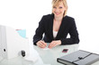 Smiling businesswoman seated at a desk in a office