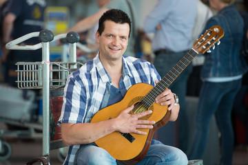 mann mit gitarre wartet am gepäckschalter